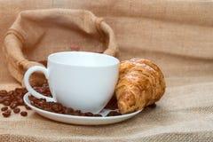 咖啡杯用新月形面包和豆在表上 图库摄影