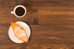 咖啡杯用新月形面包在一张黑暗的木桌上的早餐,顶视图 图库摄影