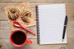 咖啡杯用曲奇饼和笔记薄与笔 免版税库存照片