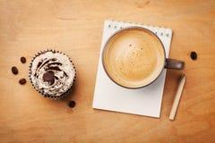咖啡杯用杯形蛋糕、笔记本和铅笔在从上面土气桌上,早晨好或者玩得高兴概念 库存照片