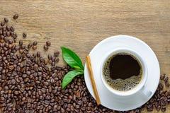 咖啡杯用豆、肉桂条和绿色叶子在木桌上 库存照片