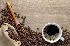 咖啡杯用豆,木匙子和大麻袋装在木桌上的袋子 免版税库存照片
