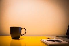 咖啡杯笔记本和膝上型计算机在桌上与灯在夜间, 免版税图库摄影