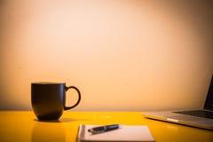 咖啡杯笔记本和膝上型计算机在桌上与灯在夜间, 库存图片