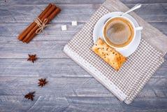 咖啡杯茶碟匙子 香草棍子 八角和灰色餐巾 库存照片