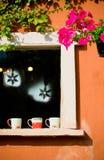 咖啡杯被安置在装饰的葡萄酒窗口 图库摄影