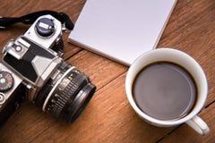 咖啡杯顶视图和照相机和笔记本在木葡萄酒制表背景 库存照片