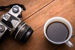 咖啡杯顶视图和照相机在木葡萄酒制表背景 免版税库存图片
