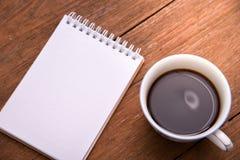 咖啡杯顶视图和笔记本在木葡萄酒制表背景 免版税库存图片