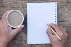 咖啡杯顶视图有手文字和空白的笔记本的和 库存照片