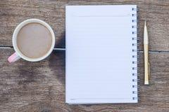 咖啡杯顶视图有空白的笔记本和金笔的在木头 库存照片