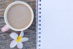 咖啡杯顶视图有羽毛花和空白的笔记本的 图库摄影