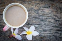 咖啡杯顶视图有羽毛花的在木桌bac 库存照片
