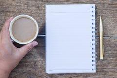 咖啡杯顶视图用手和空白的笔记本和金pe 免版税图库摄影