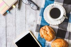 咖啡杯顶视图用面包、桌布、笔记本、笔、玻璃和片剂在木桌背景 免版税库存图片