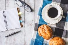 咖啡杯顶视图用面包、桌布、笔记本、笔和玻璃在木桌背景 免版税库存照片