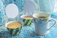 咖啡杯,在鞋带餐巾,与拷贝空间的卡片的杯形蛋糕 库存照片