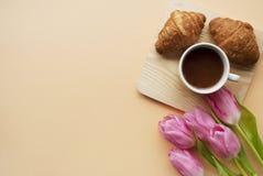 咖啡杯,新月形面包,在桃子背景的桃红色郁金香与您的文本的地方 早餐构成 平的位置 免版税库存照片
