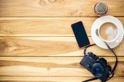 咖啡杯,照相机,在木头的巧妙的电话 库存图片