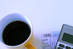 咖啡杯,美国报税表1040和计算器 免版税库存图片