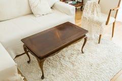 咖啡桌在有沙发和葡萄酒装饰的明亮的客厅 免版税库存图片