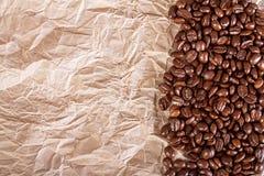 咖啡油煎的豆在被击碎的纸背景的 库存图片