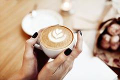 咖啡热奶咖啡在妇女手上,从上面看法,在咖啡馆的玫瑰色花 免版税库存照片