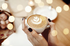 咖啡热奶咖啡在妇女手上,从上面看法, bokeh,在咖啡馆的玫瑰色花 免版税图库摄影