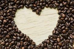 咖啡爱,咖啡豆在一块木头做心脏形状 免版税库存图片