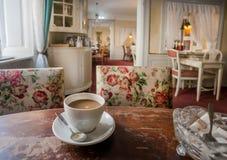 咖啡用在减速火箭的桌上的牛奶在老餐馆里面,有葡萄酒家具和历史家舒适房间的  免版税库存图片