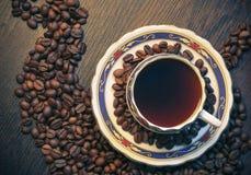 咖啡用在木背景的咖啡豆与从水平的油罐顶部角钢的杯子 免版税库存图片