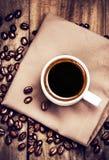 咖啡用在棕色餐巾的咖啡豆在木桌上 库存图片