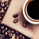 咖啡用在棕色餐巾的咖啡豆在木桌上 免版税库存图片