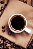 咖啡用在棕色餐巾的咖啡豆在木backg 库存图片