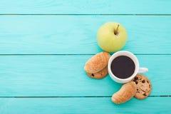 咖啡用在蓝色木桌上的新月形面包 选择聚焦 复制空间并且嘲笑  免版税库存照片