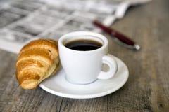 咖啡用新月形面包和报纸与笔 库存照片