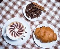 咖啡用新月形面包和豆在板材顶视图 免版税库存照片