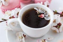 咖啡用桃红色蛋白杏仁饼干和花 免版税库存照片