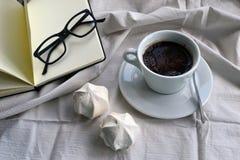咖啡用点心和一个笔记薄与玻璃 免版税库存照片