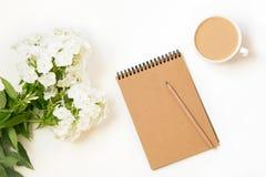 咖啡用牛奶,福禄考花,在白色桌上的scretch书从上面 女性工作和创造性的书桌 大模型 平的位置 免版税库存图片