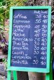 咖啡用英语写的菜单手与白垩在绿色框架黑板 免版税库存照片