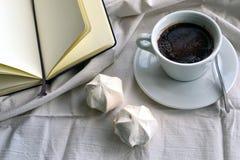 咖啡用蛋白软糖和一个笔记本在床上 免版税库存图片
