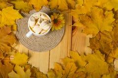 咖啡用蛋白软糖,许多在桌上的下落的秋叶 图库摄影