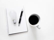 咖啡电灯泡和笔记薄 免版税库存照片