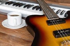 咖啡电镀吉他、钢琴和盖帽  库存照片