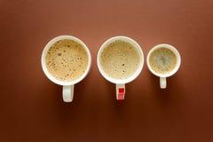 咖啡的不同的类型 后,热奶咖啡和浓咖啡在棕色背景 顶视图 平的位置 图库摄影