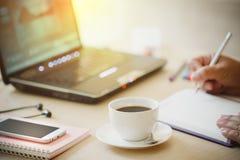 咖啡的关闭和巧妙的电话用商人的手使用便携式计算机的和在木书桌办公室w写笔记本 库存图片