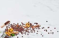 咖啡的概念用不同的香料的从一个玻璃瓶子溢出 免版税库存图片
