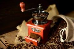 咖啡碾和咖啡豆在黑暗的背景 免版税图库摄影