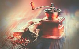 咖啡碾和烤咖啡豆 与充分粗麻布大袋的磨咖啡器在木桌的烤豆 库存照片
